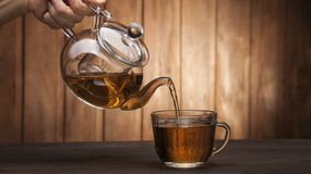Poured from a teapot. Cup of tea on a wooden table stock images