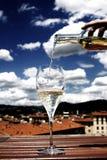 Pourig vin in i ett exponeringsglas Arkivbild