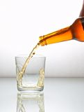Pouring. Beer pouring into glass on a white reflect background Royalty Free Stock Images