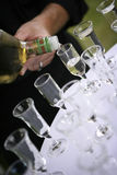 Pouring alcohol in glasses. On a white table Royalty Free Stock Images