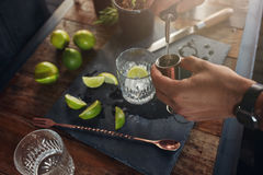 Pouring alcohol in jigger to prepare a cocktail Stock Photos
