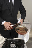 Pouring alcohol onto the steak to flambe Stock Images