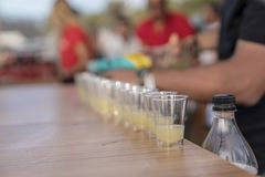 Pouring alcoholic beverage into shot glasses in a row stock photography