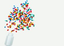 Pouring antibiotics capsule pills into plastic bottle. On white background with copy space. Drug storage, antibiotic drug use with reasonable, health policy and stock photo