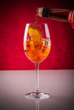 Pouring aperitif in a glass over ice cubes and orange slice Royalty Free Stock Images