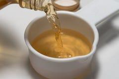 Apple cider vinegar. Pouring apple cider vinegar into a measuring cup royalty free stock photos