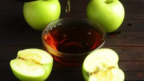 Pouring Apple cider vinegar into a small glass bowl standing on a wooden stand next to several green apples on a wooden. Background, top view stock video footage
