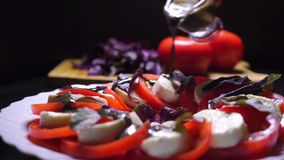 Pouring balsamic sauce on tomatoes and mozzarella cheese salad stock video footage
