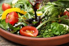 Pouring balsamic vinegar to fresh vegetable salad on plate royalty free stock photo