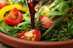 Pouring balsamic vinegar to fresh vegetable salad on plate stock photos