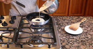Pouring batter into frying pan stock video footage