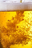 Pouring of beer. The bubbles of air rise in glass with beer royalty free stock image