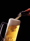 Pouring Beer. A view of refreshing beer being poured in to a glass, on black studio background Royalty Free Stock Photo