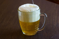 Pouring beer from bottle into mug at bar Royalty Free Stock Photography