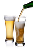Pouring beer into glass. Beer being pour on a glass over a white background Stock Photo