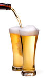 Pouring beer into glass. Beer being pour on a glass over a white background Royalty Free Stock Image