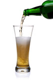 Pouring beer into glass. Beer being pour on a glass over a white background Stock Photos