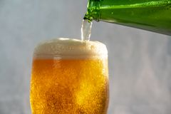 Pouring beer into a glass from a bottle stock photo