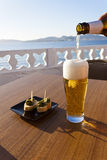 Pouring beer in a glass near the sea. Royalty Free Stock Photo