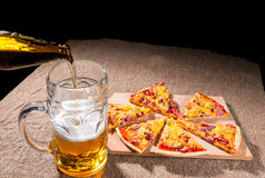 Pouring Beer into Glass next to Pizza Slices Royalty Free Stock Photo