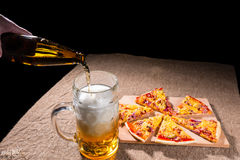 Pouring Beer into Glass next to Pizza Slices Royalty Free Stock Photography