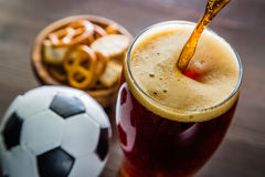 Pouring beer into glass with snacks and football. Closeup stock photo