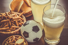 Pouring beer into glass with snacks and football. Toned stock photo