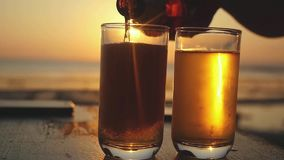 Pouring Beer in a Glass on a tropical Beach at beautiful Sunset with lens flare effects in slow motion. 1920x1080. Pouring Beer in a Glass on a Beach at stock video