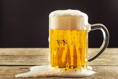 Pouring beer into a glass on a wooden table. Alcoholic beverages. Alcohol-free beer. Sale of beer to the bar. Pouring beer into a glass on a wooden table Stock Photography
