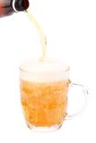 Pouring beer into mug isolated. Over a white background Royalty Free Stock Photos