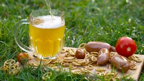 Pouring beer with pretzel, sausages and tomatoes royalty free stock images