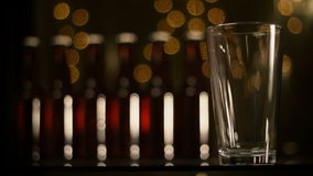 Pouring beer. Stock video of beer being poured into glass, defocused background of lights and beer bottles stock footage