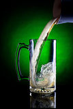 Motion of beer being poured. Pouring a big mug of beer in a studio setting Royalty Free Stock Image