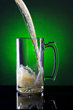 Motion of beer being poured. Pouring a big mug of beer in a studio setting Stock Image