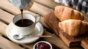 Pouring black coffee into cup. Tasty breakfast. Coffee, croissants, jam stock video