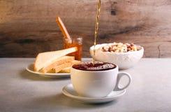 Pouring black tea into cup Royalty Free Stock Photos