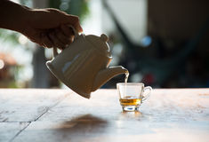 Pouring the black tea in a glass. On table Stock Images