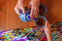 Pouring black tea from teapot in bowl in uzbek restaurant Stock Image