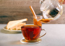 Pouring black tea in to transparent glass Royalty Free Stock Image