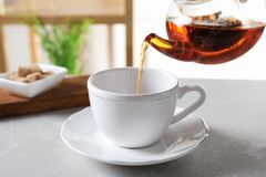 Pouring black tea into white porcelain cup. On gray table royalty free stock photo