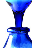 Pouring Blue. Glass stem behind bottle giving feeling of pouring liquid blue Stock Image