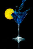 Pouring Blue Martini into the Martini Glass with Lemon. At the black background Royalty Free Stock Photography