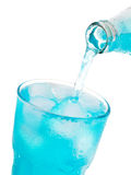 Pouring blue soda into glass with ice from bottle Stock Photo