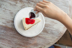 Pouring blueberry sauce topping on cheese cake. Stock Photo
