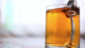 Pouring boiling water into a glass and brewing tea. Bags stock video