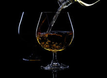 Pouring brandy into a glass. From bottle Royalty Free Stock Images