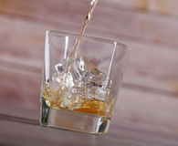 Pouring brandy into glass with ice Royalty Free Stock Photography