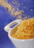 Pouring brown sugar into a bowl Stock Images