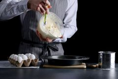 Pouring cake dough into baking tin. man hold bowl and pouring batter royalty free stock photos