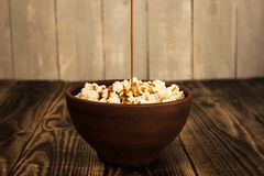 Pouring caramel into bowl of popcorn Royalty Free Stock Images